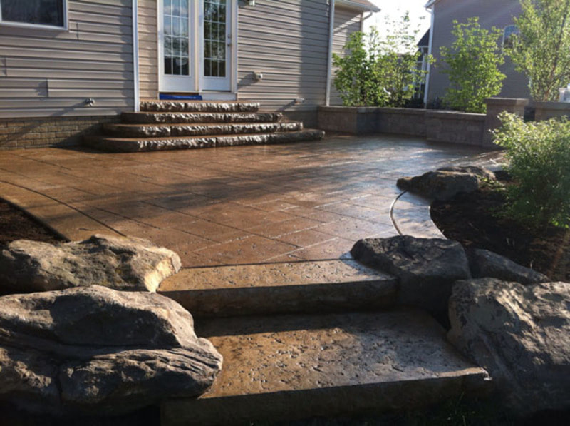 stamped concrete patio with boulders surrounding steps
