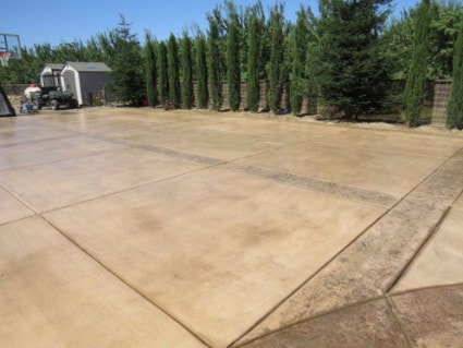 Large stamped concrete pad in front of a shed with colored concrete accents