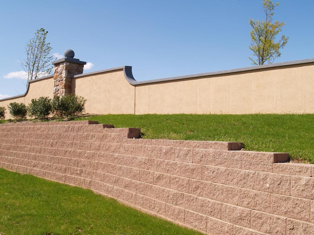 Six foot high retaining wall next to grass for erosion control