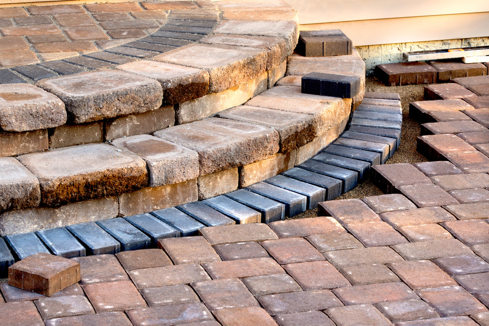 paved walk way leading to stone stairs, there are different colored bricks as accents near stairs